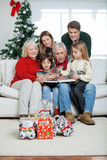 Family Looking At Book In House
