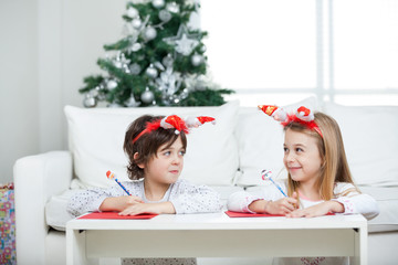 Siblings Writing Letter To Santa Claus During Christmas