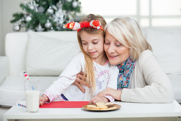 Grandmother Assisting Girl In Writing Letter To Santa Claus