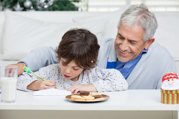 Grandfather Assisting Boy In Writing Letter To Santa Claus