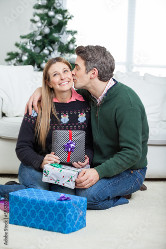 Man Kissing Woman On Cheek With Christmas Gifts