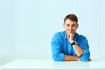 Young happy businessman in blue shirt sitting