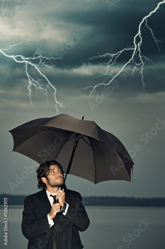 Businessman protecting himself from thunders