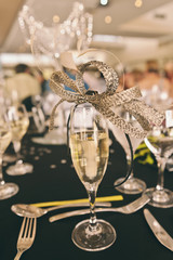 woman's fascinator on champagne glass