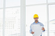 Architect in yellow hard hat looking at blueprint in office