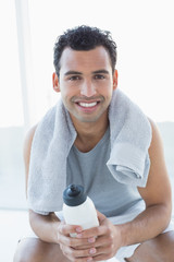 Man with towel around neck holding water bottle in fitness studi