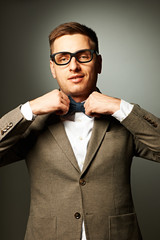 Confident nerd in eyeglasses adjusting his bow-tie