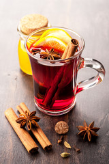 Hot wine with honey and spices in a glass cup