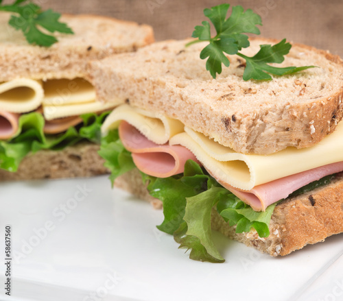Fresh ham and cheese on white sandwich in rustic kitchen setting - 58637560