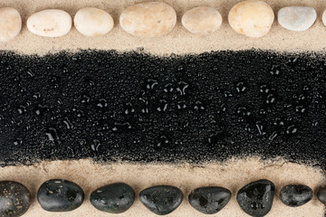 Black and white Zen stones on sand and water drops