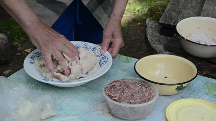 Senior woman hands prepare gradered potatoes for dumplings meal