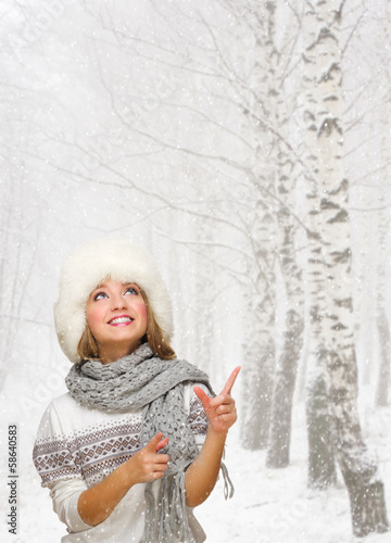 Girl shows pointing gesture at winter forest