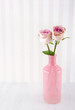 Pink roses in a glass bottle on wooden background