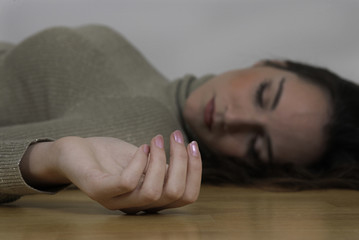Dead woman curled hand lying on floor