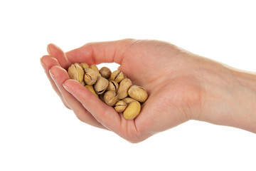 Salted and roasted pistachio nuts in a hand