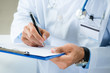 Male Doctor Writing On Medical Document