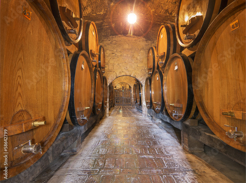 Wine barrels stacked in the old cellar of an Italian winery.