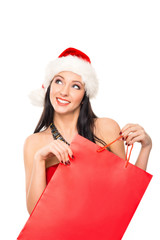 A happy woman in a Christmas hat holding a shopping bag