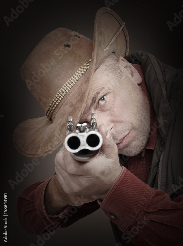Cowboy with shotgun aiming at you. Gun control concept.