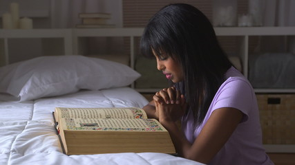 African American girl praying with Bible on bed