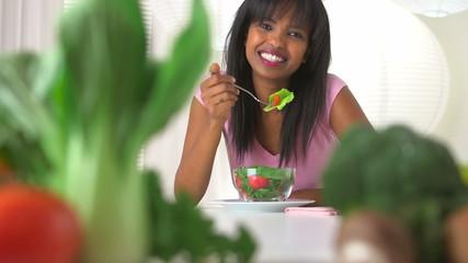Rack focus between woman eating salad and fresh vegetables