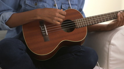 Close up of girl strumming ukulele