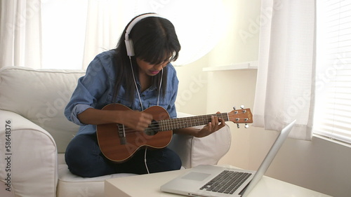 Black girl singing and playing ukulele