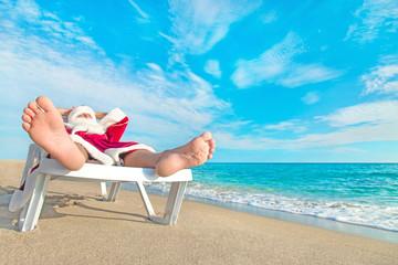 sunbathing Santa Claus relaxing in bedstone on beach - Christmas