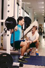 Personal trainer working with client in gym helping with squats