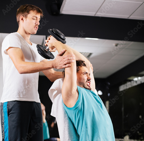 Personal trainer working with his client in gym helping him with