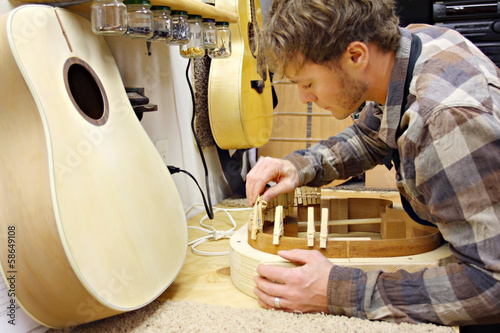 Woodworker Building Guitar in Workshop