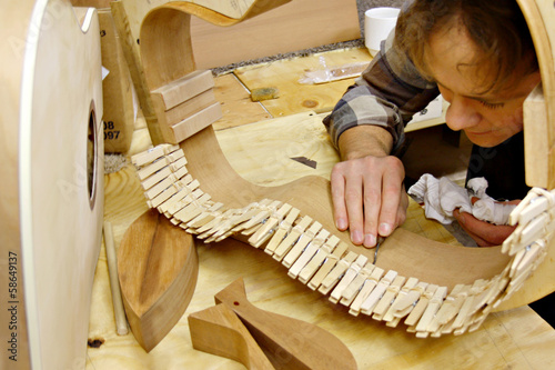 Luthier Building Guitar in Workshop