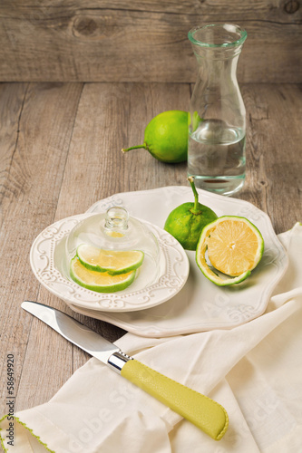 Lemon on plate and water on wooden table