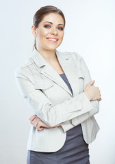 Portrait of happy young business woman crossed arms against whi