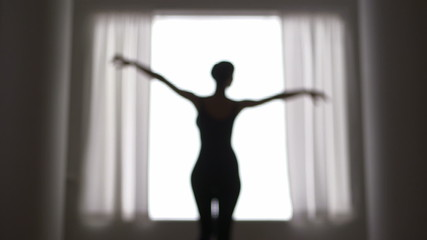 Out of focus woman dancing in front of window