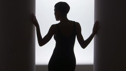 Rear view of black woman dancing in front of bright light