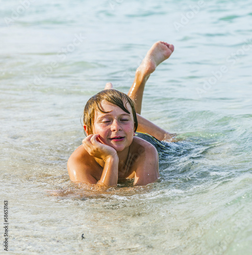 boy enjoys lying at the beach in the surf
