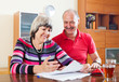 Happy mature couple reading financial documents