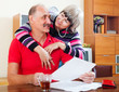 mature man with wife reading financial documents
