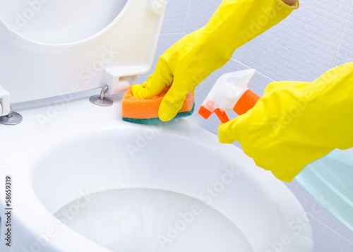 Hands on yellow gloves cleaning a WC
