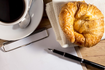 blank white notebook,pen,cup of coffee and  croissant on the de