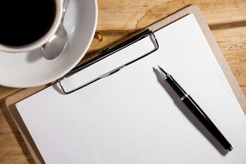 blank white notebook, pen and cup of coffee on the desk