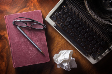 Old typewriter with book,pen and eyeglasses