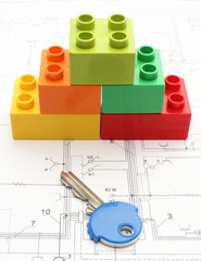 Colorful building blocks and key on housing plan