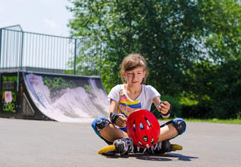 Young teenage roller skater with her helmet