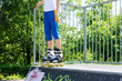 Legs of a young roller skater on a cement ramp