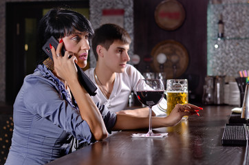 Two friends at the bar with a woman on a mobile