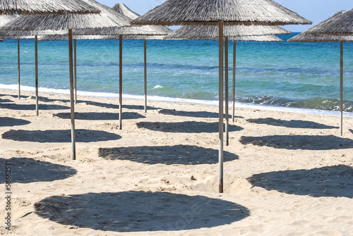 Parasols and shades on sea beach in sunny day