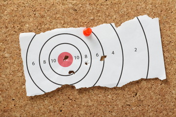 Target bullseye with bullet holes on a cork notice board