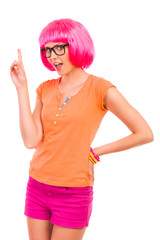 Young woman in black glasses and pink wig pointing up.